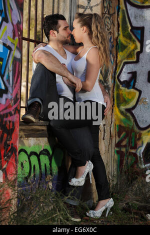 Young couple kissing against a barred window in a ruined building covered in graffiti - Stock Photo