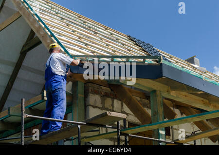 A worker standing on the scaffolding and finishing a roof - Stock Photo