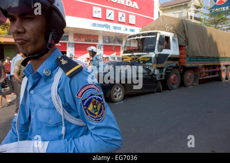 A Cambodian policeman walks near a head on collision between a car and a truck on National Road 7 in Kampong Cham, - Stock Photo