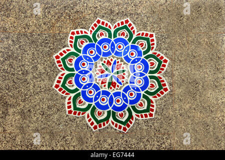 Printed, colorful, geometrical pattern of rangoli stuck on mosaic tiled floor - Stock Photo