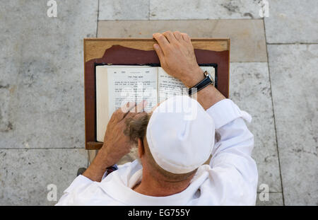 A jewish man is reading in the torah near the wailing wall in Jerusalem - Stock Photo