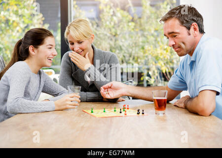 Family playing ludo at home - Stock Photo