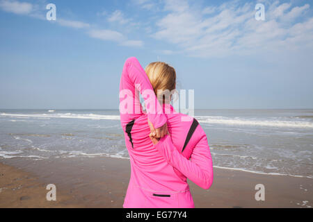 Belgium, Flanders, woman doing stretching exercise on the beach - Stock Photo