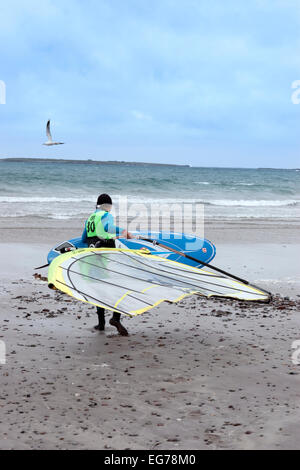 windsurfer getting ready to surf on the beach in the maharees county kerry ireland - Stock Photo
