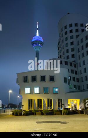 Germany, Duesseldorf, media harbor, Neuer Zollhof and Rhine Tower at night - Stock Photo