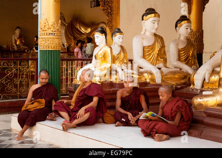 Four buddhist monks sitting beneath four Buddha statues, Shwedagon Pagoda, Yangon, Myanmar ( Burma ), Asia - Stock Photo