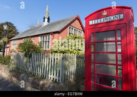 Village of Aldford, England. A Grade II listed K5 red telephone box with Aldford Village Hall in the background. - Stock Photo