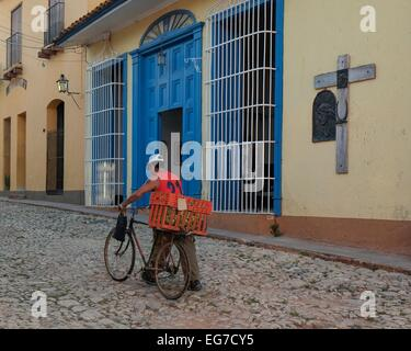 A Cuban male pushes his bicycle past a religious memorial on a cobbled street in Trinidad, Cuba. - Stock Photo