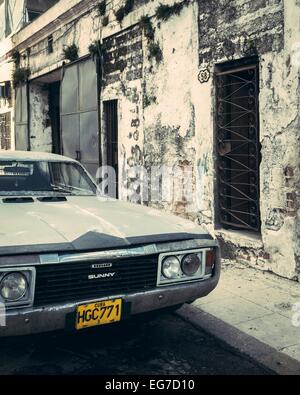 A Nissan Sunny retro car parked in a decaying street, Havana, Cuba. - Stock Photo