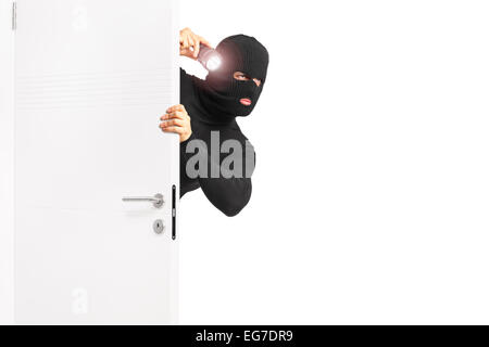 Burglar with flashlight entering through a door isolated on white background - Stock Photo