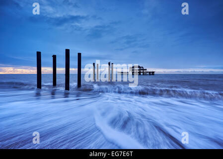 The decaying remains of Brighton's West Pier at sunrise with the tide coming in. - Stock Photo