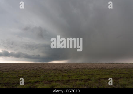 A powerful tornado warned supercell thunderstorm rolls across the Texas landscape with a large wall cloud and green - Stock Photo