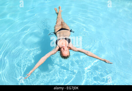 Caucasian lady floating in swimming pool. - Stock Photo