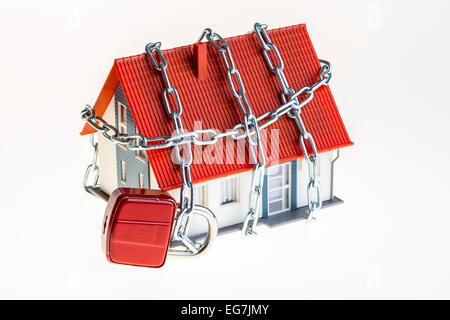 Symbolic image, safety at home, burglary prevention, steel chain and lock around a model house, - Stock Photo