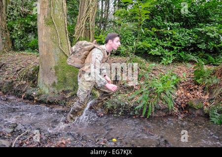 Bangor, Northern Ireland. 18th February, 2015. A soldier runs through a small stream Credit:  Stephen Barnes/Alamy - Stock Photo