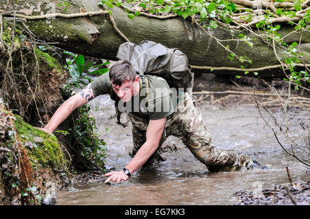 Bangor, Northern Ireland. 18th February, 2015. A solder from the Royal Irish Regiment climbs under a tree through - Stock Photo