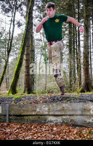 Bangor, Northern Ireland. 18th February, 2015. A soldier jumps an obstacle during a cross country training exercise. - Stock Photo