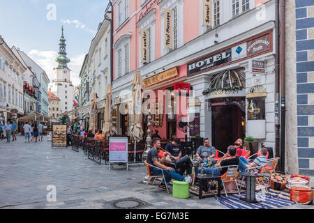 Tourists at a terrace cafe in Venturska Michalska the Old Town´s main street with Michael's Gate in background. - Stock Photo