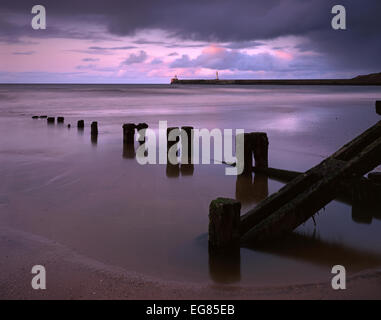 Groyne and harbour wall at Aberdeen seafront at sunset, Aberdeenshire. - Stock Photo