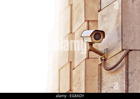 Security CCTV camera mounted on the building wall as apart of private property protection system or Big Brother - Stock Photo