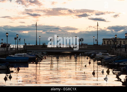 Trieste, Italy - Silhouettes of people on the bridge on the Canal Grande in Trieste, Italy - Stock Photo
