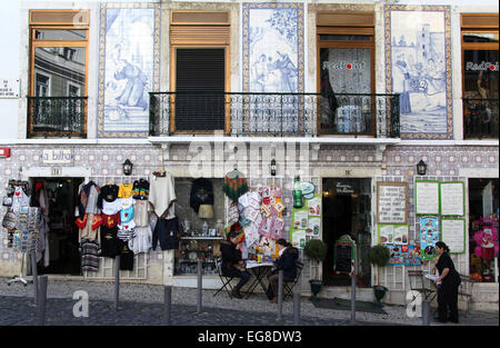 Tourists sitting outside a cafe in the popular sightseeing Alfama district of Lisbon in Portugal - Stock Photo
