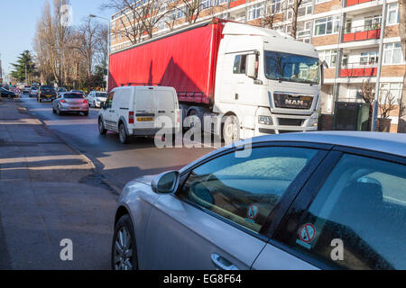 Car parked on the pavement of a busy road with heavy traffic in a residential area. West Bridgford, Nottinghamshire, - Stock Photo