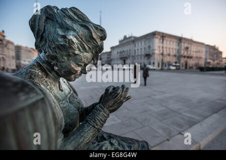 Trieste, Italy - The 'Sartine' statue is lighted from the last rays of the sun while behind people walk on Piazza - Stock Photo