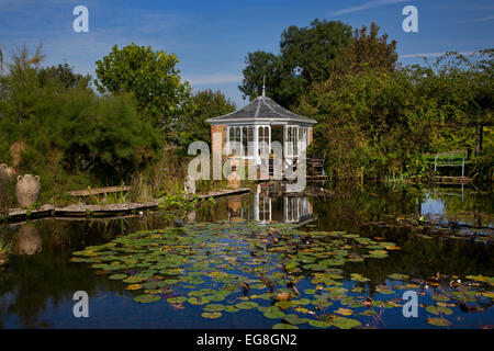 Large garden pond in summer with brick summerhouse and seating overlooking water and water lilles,Garden,Oxfordshire,England - Stock Photo