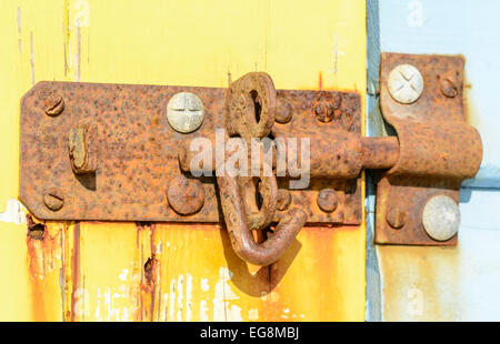 Old rusty lock on a wooden shed door. - Stock Photo