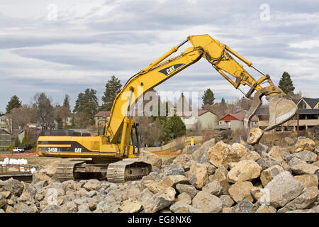 Heavy earth-moving shovels and other equipment working on changing the river channel of the Deschutes River in Bend, - Stock Photo