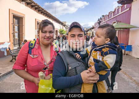 proud happy young Mexican couple with daddy holding toddler son in pedestrian street 16 September San Cristobal - Stock Photo