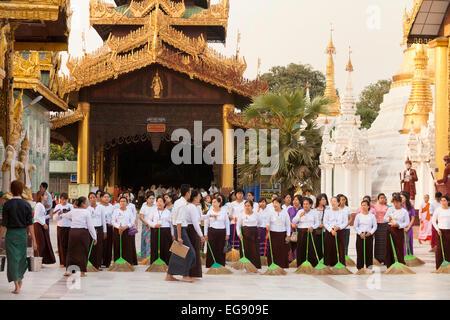Young women sweeping the ground at sunset, the Shwedagon Pagoda, Yangon, Myanmar ( Burma ), Asia - Stock Photo