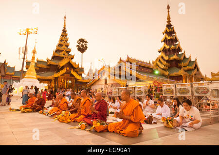 Buddhist monks and local people worshipping at the Shwedagon Pagoda, Yangon, Myanmar ( Burma ), Asia - Stock Photo