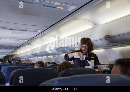Chicago, Illinois - A Southwest Airlines flight attendant serves drinks to passengers on a flight to Denver. - Stock Photo