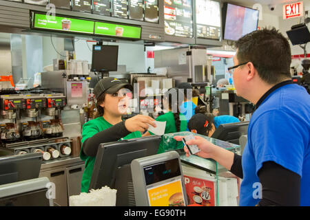 Chicago, Illinois - A young woman waits on a customer at a McDonald's fast food restaurant at Midway Airport. - Stock Photo