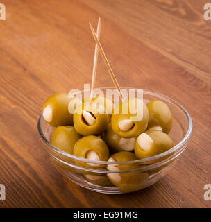 Green garlic stuffed olives in a glass bowl on dark wood table - Stock Photo