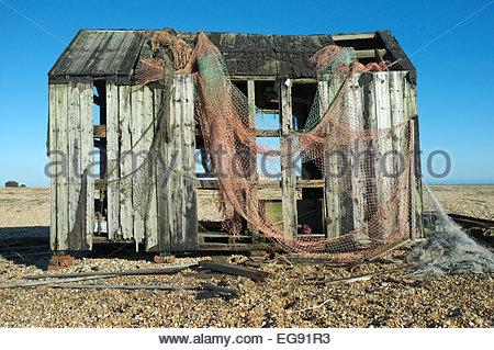 Old dilapidated fishing hut with abandoned fish netting, on Dungeness beach, Kent, UK. - Stock Photo