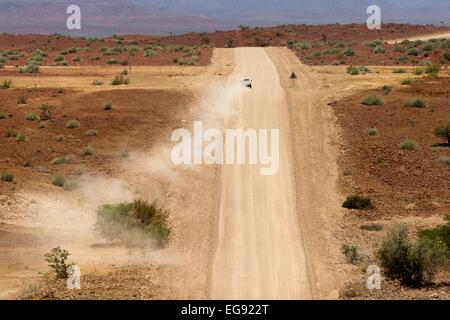 A white 4x4 vehicle drives away from the camera on a dry dusty track in northern Namibia, Africa. - Stock Photo