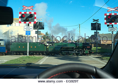 View from a car of narrow gauge steam loco Typhoon of the RH&DR passing over a level crossing in Greatstone-on-Sea, - Stock Photo