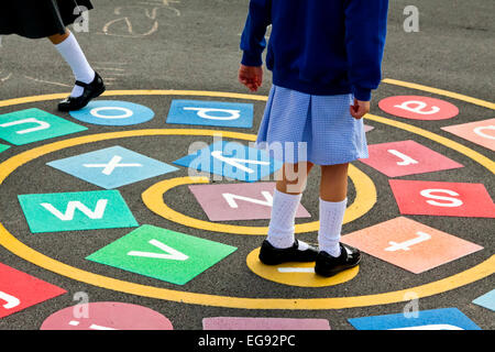 Primary schoolchildren playing in a school playground at break time with alphabet games marked out on the asphalt - Stock Photo