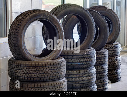 Stacks of tires, with tread patterns for various driving conditions, for sale in an automotive repair garage. - Stock Photo