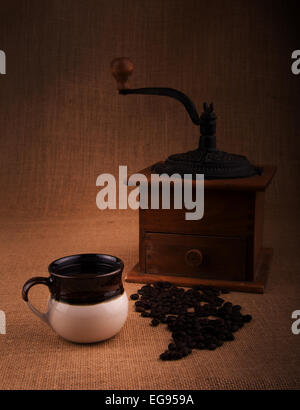 Cup of coffee with beans and an old grinder on the background, a warm toned image with vignette - Stock Photo