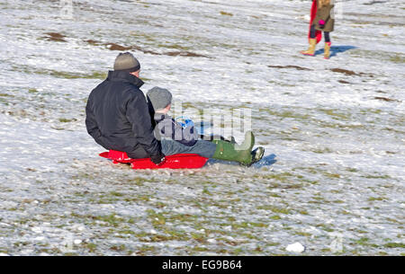 Man and boy on sledge together sledging downhill on snowy hillside Caldbeck fells, Lake District, Cumbria, England - Stock Photo