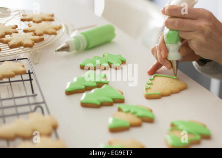 Woman decorating cookies with green colored icing - Stock Photo