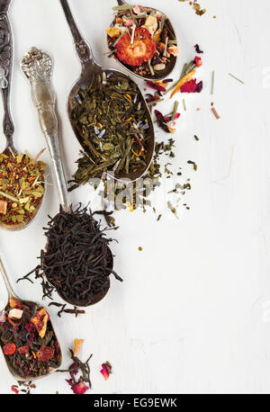 Different types of tea leaves in spoons - Stock Photo