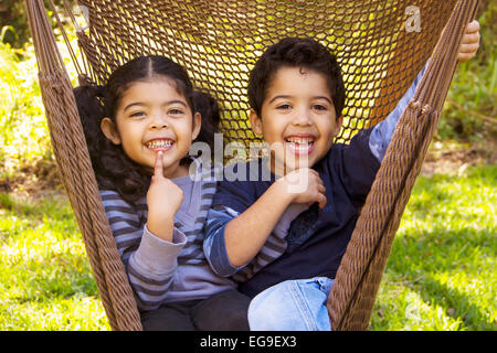 Twin brother and sister sitting in a hammock pulling funny faces - Stock Photo