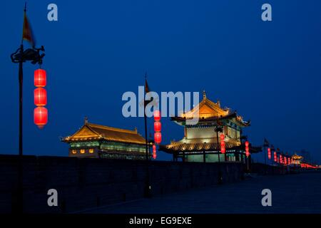 China, Shaanxi, Xian, Ancient city wall in front of traditional buildings at night - Stock Photo