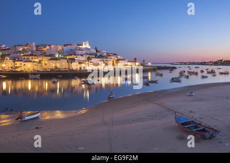 Portugal, Algarve, Ferragudo, Illuminated town and boats in harbor - Stock Photo