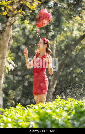 Woman with red heart shape balloon in a park - Stock Photo